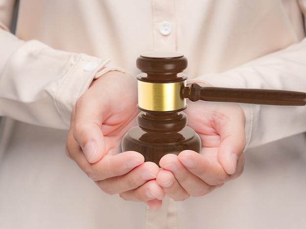 Ręka trzyma sędziego młotka do renderowania 3d