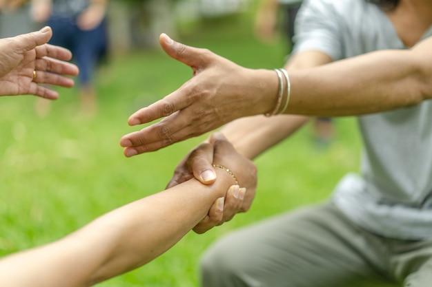 Ręka trzyma się razem w społeczności w ogrodzie / parku.