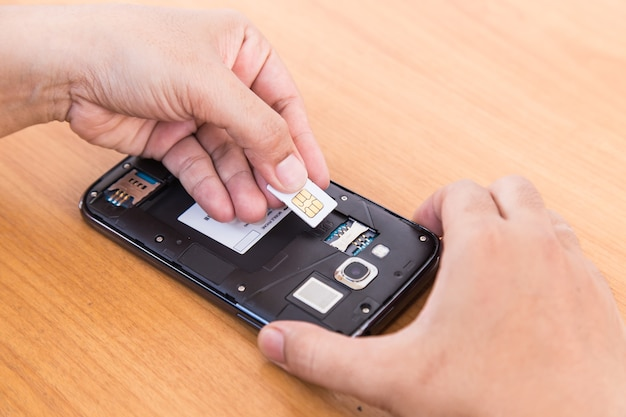 Ręka trzyma sim kartę i smartphone na tle drewna