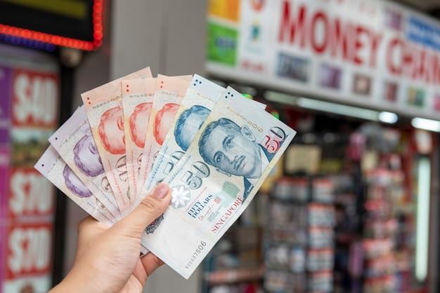 Ręka trzyma singapur dolarowych banknoty, wymiany walut pojęcie