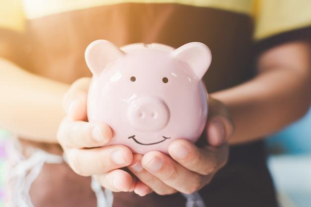 Ręka trzyma skarbonkę. oszczędź pieniądze i inwestycje finansowe