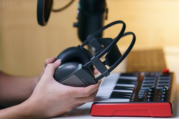 Ręka trzyma słuchawki w pobliżu konsoli miksowania dźwięku. sprzęt do studia muzycznego.