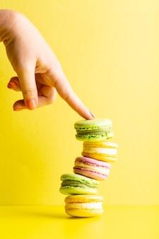 Ręka trzyma smaczne makaroniki na żółtym zdjęciu wysokiej jakości