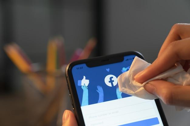 Ręka trzyma smartfon i ekran facebooka na telefonie, media społecznościowe używają do wymiany informacji i sieci.