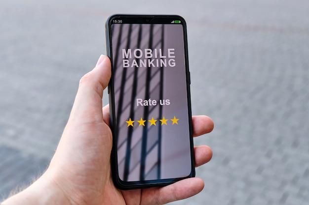 Ręka trzyma smartfon z interfejsem bankowości mobilnej i napisem oceń nas 5 gwiazdkami