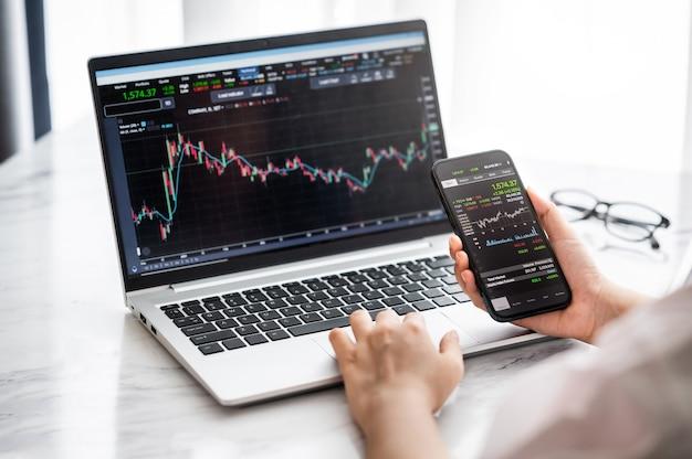 Ręka trzyma smartfona z danymi giełdowymi i używa wykresu i wykresu wyświetlacza laptopa do analizy i sprawdzenia przed handlem akcjami online