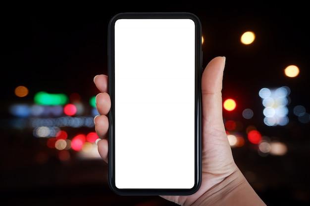 Ręka trzyma smartphone rezygnować pusty ekran nad niewyraźne sygnalizacja świetlna w nocy