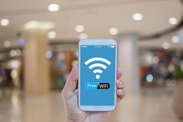 Ręka trzyma smartphone z bezpłatnym wifi na ekranie nad niewyraźne w tle centrum handlowego