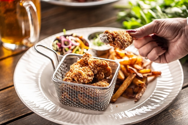 Ręka trzyma smażoną bryłkę kurczaka zanurzoną w białym sosie na talerzu z frytkami