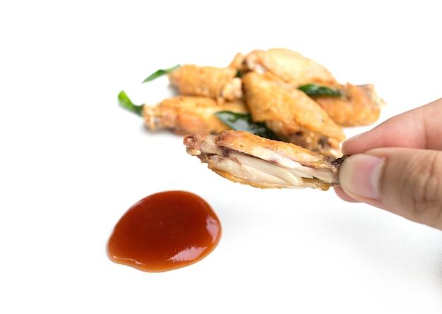 Ręka trzyma smażone skrzydełka z kurczaka i keczup na białym tle