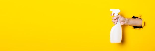 Ręka trzyma spray ze środkiem czyszczącym lub wodą na żółto