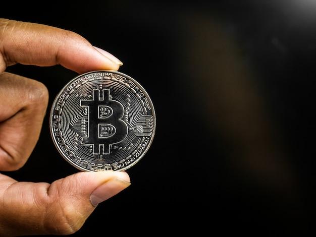 Ręka trzyma srebrną bitcoinę.
