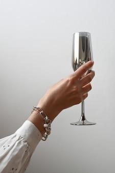 Ręka trzyma srebrny kieliszek