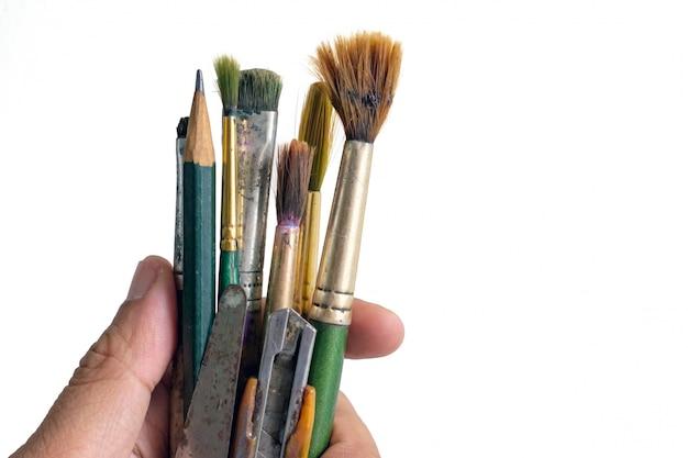 Ręka trzyma stare używane pędzle. używać brudni farb muśnięcia na białym tle
