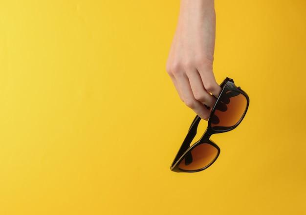 Ręka trzyma stylowe okulary przeciwsłoneczne na żółtym tle. studio mody strzał