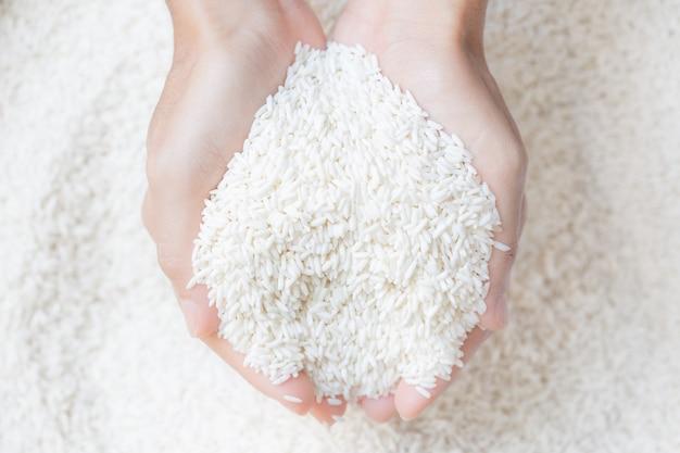 Ręka trzyma surowy biały ryż