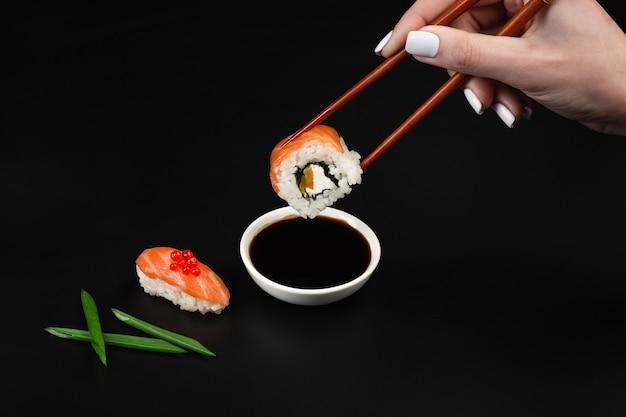 Ręka trzyma sushi nad miską z sosem sojowym na czarnym stole.
