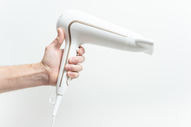 Ręka trzyma suszarkę do włosów zbliżenie