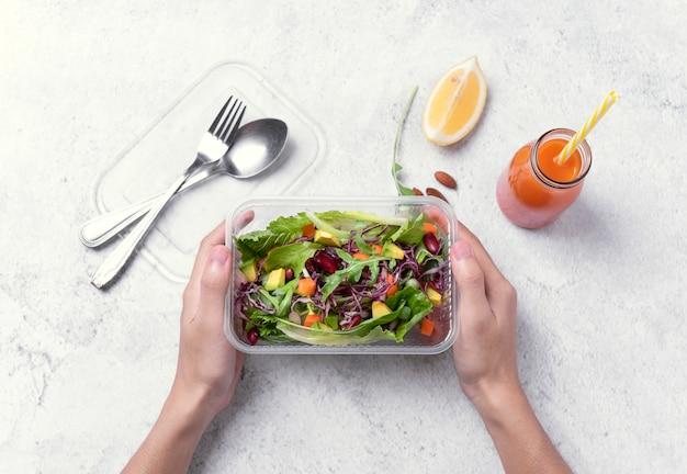 Ręka trzyma świeżego zdrowej diety lunchu pudełko z jarzynową sałatką na stołowym tle.
