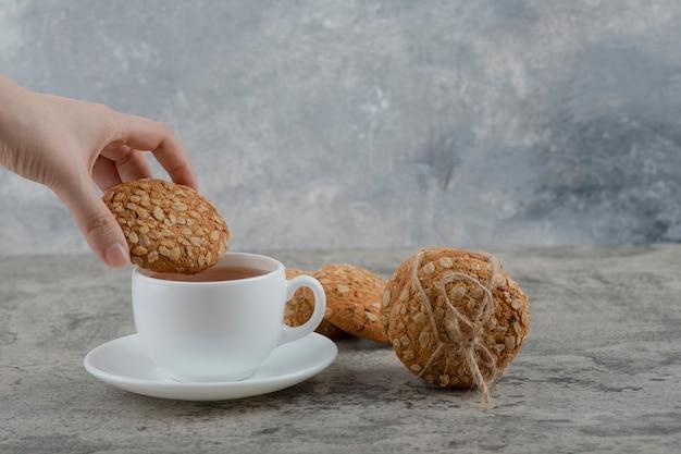 Ręka trzyma świeży herbatnik na czarnej herbacie.