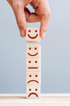 Ręka trzyma symbol twarzy uśmiechu na drewnianych klockach