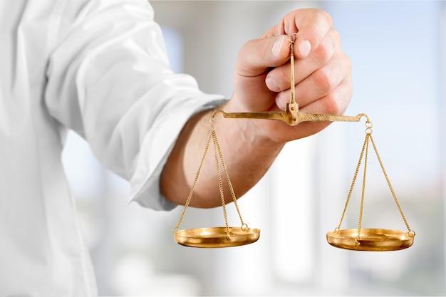 Ręka trzyma symbol wagi sprawiedliwości na niebieskim tle