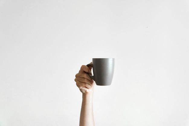 Ręka trzyma szarą cupcoffe om biel. senny poranek. copyspace