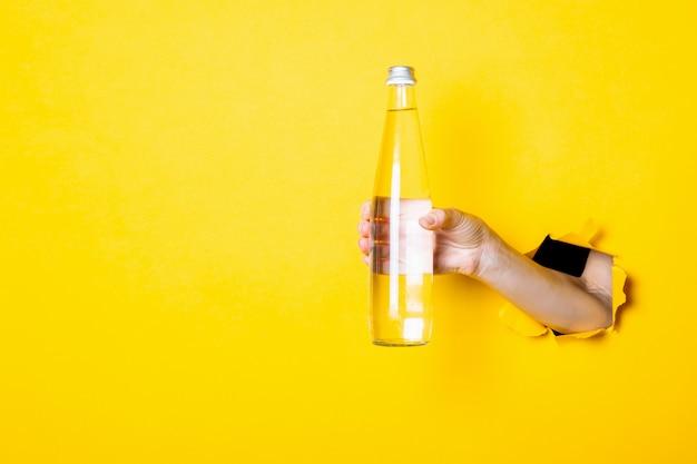 Ręka trzyma szklaną butelkę z wodą na jasnożółtym tle
