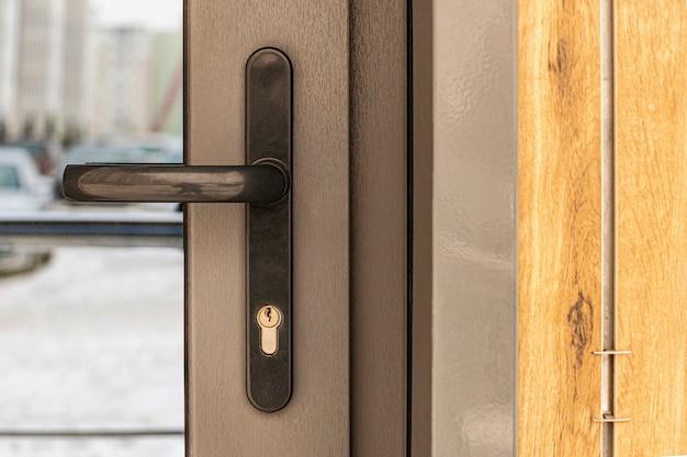 Ręka trzyma szklane drzwi wejściowe ulicy. drzwi z podwójnymi szybami. wejście do biurowca.