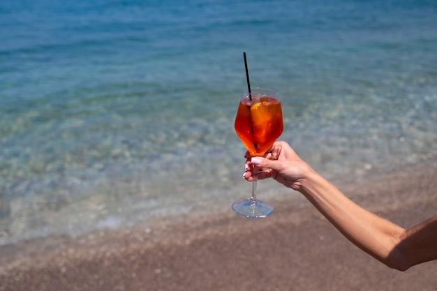 Ręka trzyma szklankę koktajlu aperol spritz na tle morza