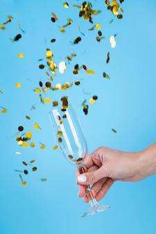 Ręka trzyma szklankę otoczoną złotymi cekinami i konfetti