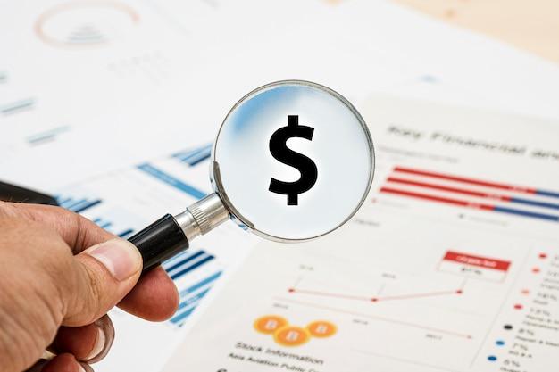 Ręka trzyma szkło powiększające do wyszukiwania znak dolara amerykańskiego i sprawozdanie finansowe.