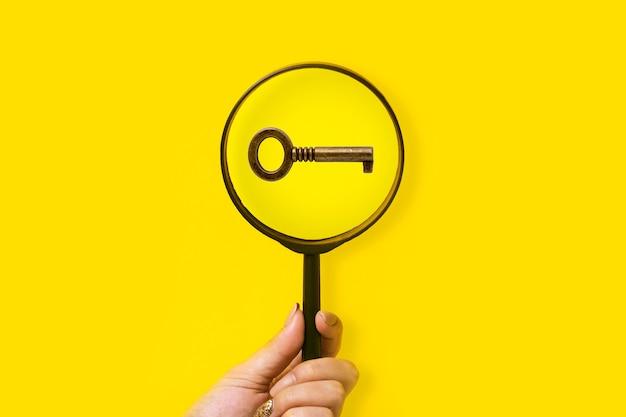 Ręka trzyma szkło powiększające nad kluczem