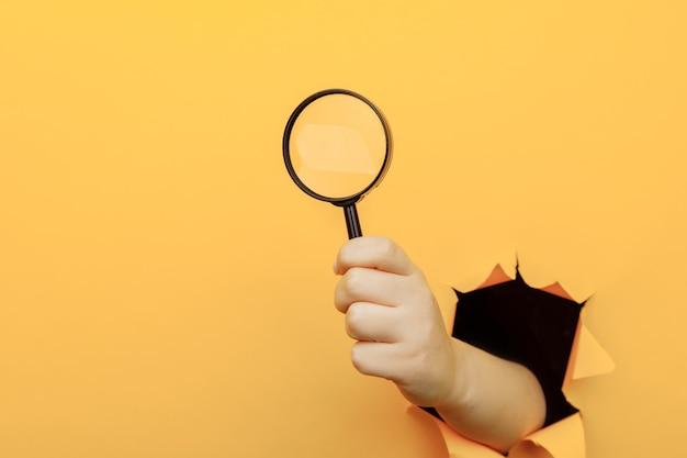Ręka trzyma szkło powiększające przez rozdarty otwór w żółtej ścianie papieru.