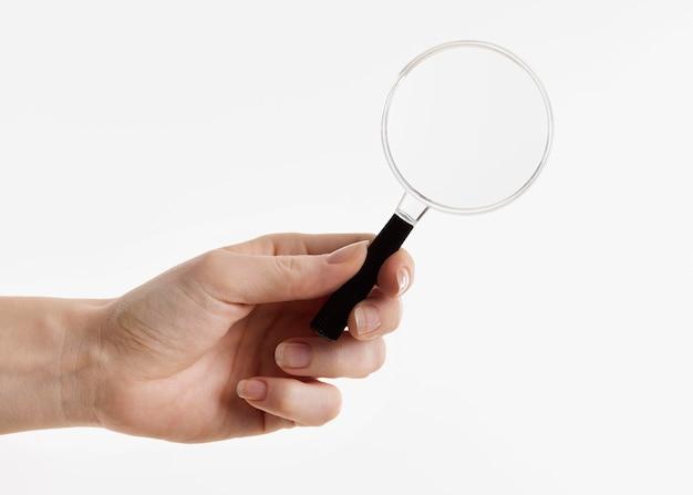 Ręka trzyma szkło powiększające