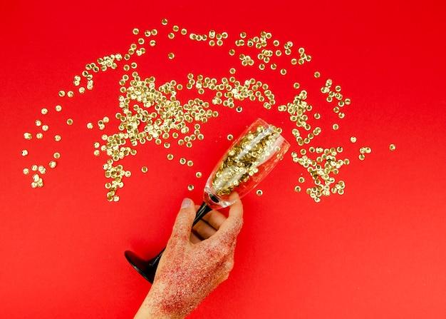 Ręka trzyma szkło ze złotym brokatem