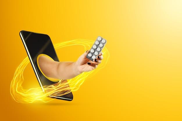 Ręka trzyma tabletki za pośrednictwem smartfona
