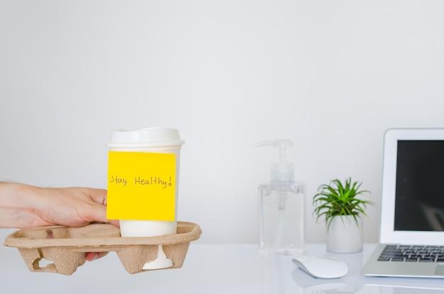 Ręka trzyma tacę kubka z kawą z żółtą nutą z napisem stay healthy, aby kibicować sytuacji wirusa covid-19 lub wirusa korony na całym świecie.