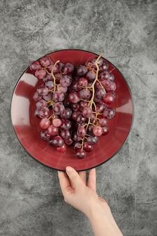 Ręka trzyma talerz świeżych winogron umieszczonych na marmurowej powierzchni.