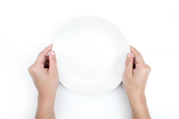 Ręka trzyma talerz w widoku z góry. na białym tle.