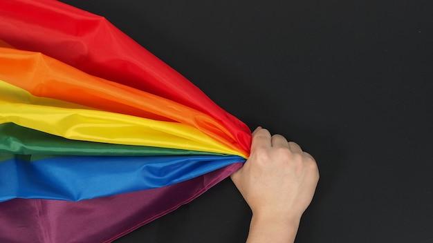 Ręka trzyma tęczową flagę na czarnym tle.