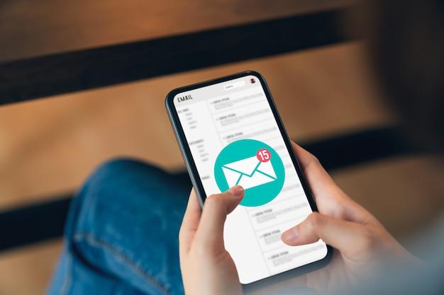 Ręka trzyma telefon i pokazuje ekran e-mail na aplikacji mobilnej.