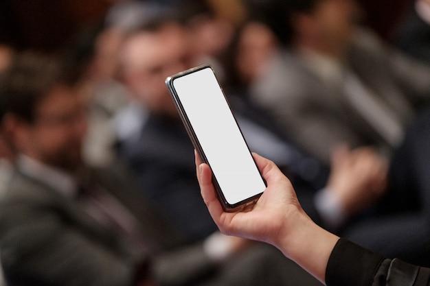Ręka trzyma telefon komórkowy na spotkaniu