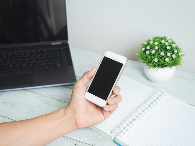 Ręka trzyma telefon komórkowy z obszarem roboczym na białym tle stołu z drewna