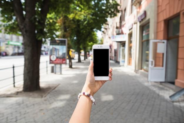 Ręka trzyma telefon komórkowy z pustym ekranem przy ulicą