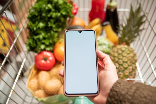 Ręka trzyma telefon z białym ekranem w koszyku spożywczym z owocami i warzywami zdrowa żywność