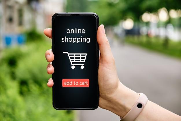 Ręka trzyma telefon z koncepcją zakupów online na wyświetlaczu