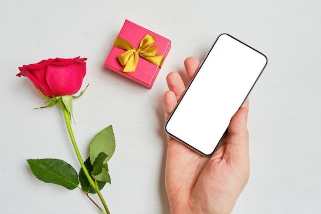 Ręka trzyma telefon z miejscem do kopiowania obok pudełka na prezent i tłem czerwonej róży