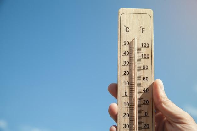 Ręka trzyma termometr na tle błękitnego nieba.