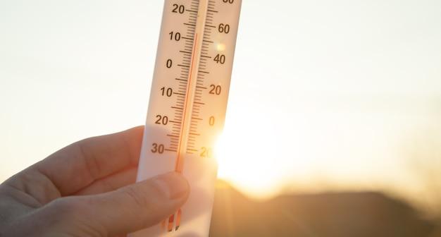 Ręka trzyma termometr na tle nieba.